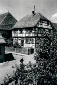 """Judengasse in Memmelsdorf. Die Synagoge steht """"in zweiter Reihe"""" hinter dem Fachwerkhaus. 1920/1930"""